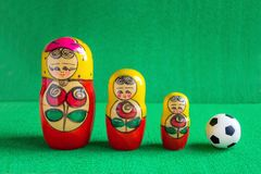 Classic black and white Football soccer ball and three red yellow russian nesting dolls Stock Photos