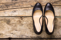 Classic black woman shoes on wooden background. Classic black woman shoes with heels on wooden background with copy space. Top view image Stock Images