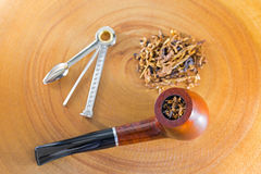 Classic blended aromatic pipe tobacco next to tool to pick ream. Selective focus of classic blended aromatic pipe tobacco next to tool to pick ream tamper Stock Photography