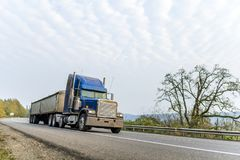 Classic blue big rig American bonnet semi truck driving with covered bulk semi trailer on the winding autumn road. Classic blue big rig American bonnet powerful royalty free stock photos