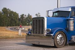 Classic blue big rig semi truck with chrome accessories running Royalty Free Stock Images