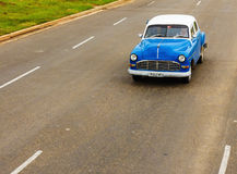 Classic blue car on Cuban street. Blue classic American car on one of the streets of Havana, where old cars are relic of Cuban revolution and still attracts many Royalty Free Stock Image
