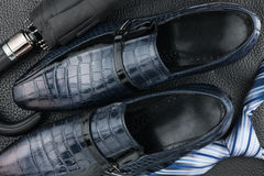 Classic blue men's shoes, tie, umbrella on the black leather. Can be used as background Royalty Free Stock Photos