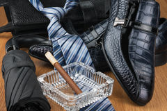 Classic blue shoes, tie, umbrella, cigar and briefcase on the wooden floor. Can be used as background Stock Photo