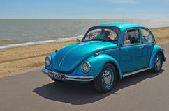 Classic Blue  Volkswagen Beetle being driven along Felixstowe seafront promenade. Royalty Free Stock Photos