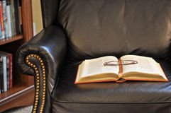 Classic Book on Reading Chair. Close-up of classic book with ribbon book mark lying open on seat of a dark leather recliner next to a book case. Glasses are Stock Photography