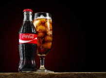 Classic Bottle of Coca-Cola and glass with drink and ice on the. MINSK, BELARUS-OCTOBER 18, 2016: Classic Bottle of Coca-Cola and glass with drink and ice on the Stock Photos