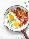 Classic Breakfast - fried eggs and bacon in a cast iron pan on a light background. Top view Stock Image