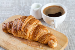 Classic breakfast interior. A cup of coffee with milk and croissant Royalty Free Stock Photography