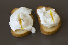 Classic breakfast - poached eggs on toast on a brown plate Royalty Free Stock Images