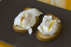 Classic breakfast - poached eggs on toast on a brown plate Stock Photo