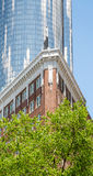 Classic Brick Apartment and Modern Blue Glass Tower. An old red brick apartment building in front of a modern, round blue glass tower Royalty Free Stock Images