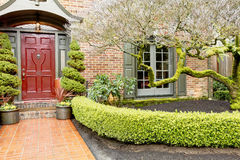 Classic brick house entrance with trim hedge Stock Photos