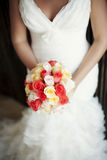 Classic bride. The classic torso of a bride holding peach and yellow roses Royalty Free Stock Images