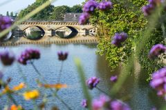 Classic bridge near the blue river through some pink flowers. In Metz in France stock photos