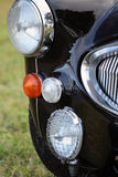 Classic British car headlight and grille. Detail of classic British car headlight and chrome grille Royalty Free Stock Photography