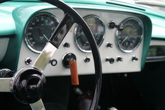 Classic sports car interior dials. Classic british car vintage interior dials, instruments, switches, shifter, and steering wheel and dashboard in green and Royalty Free Stock Photo