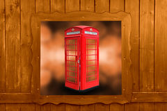 Classic British red phone booth in London UK, wooden window Royalty Free Stock Photo