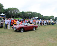 Classic British sports car driving on grass. Classic red aston martin db5 vantage driving on grass at classic concours car event in south florida Stock Image