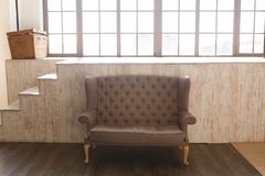 Classic brown fabric sofa and cozy lounge space with wooden backgrond and window Royalty Free Stock Photo