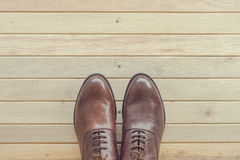 Classic brown leather men& x27;s shoes on wooden background Stock Photos