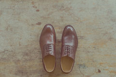 Classic brown leather mens shoes on wooden background Stock Photos