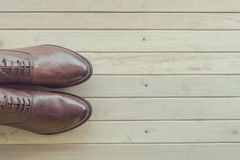 Classic brown leather mens shoes on wooden background Royalty Free Stock Photo