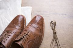 Classic brown leather shoes on wooden floor. With bag and shoelace Royalty Free Stock Photo