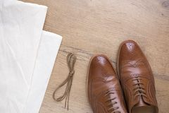 Classic brown leather shoes on wooden floor. With bag and shoelace Stock Photography