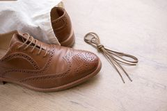 Classic brown leather shoes on wooden floor. With bag and shoelace Royalty Free Stock Photography