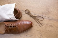 Classic brown leather shoes on wooden floor. With bag and shoelace Stock Photos