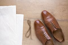 Classic brown leather shoes on wooden floor. With bag and shoelace Royalty Free Stock Images