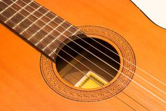Classic acoustic guitar on white background view. Classic brown orange spanish acoustic guitar on white background stock images