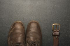 classic brown shoes and belt on wooden table. royalty free stock photos