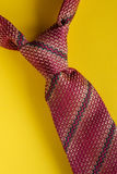 Classic brown striped tie knot close up on yellow background. Man style concept Royalty Free Stock Photography
