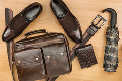 Classic brown suede shoes, briefcase, belt and umbrella on the wooden floor. Can be used as background Royalty Free Stock Images