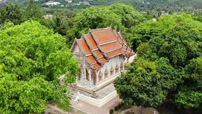 Classic Buddhist temple between forest. From above drone view Buddhist monastery between green trees near hill in. Thailand. Koh Samui. concept of tourism stock footage