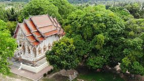 Classic Buddhist temple between forest. From above drone view Buddhist monastery between green trees near hill in. Thailand. Koh Samui. concept of tourism stock video footage