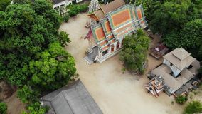 Classic Buddhist temple between forest. From above drone view classic Buddhist monastery between green trees near hill. In Thailand. Koh Samui. concept of stock footage