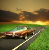 Classic buick riviera. A vintage 1971 boat tail buick riviera with white wall tires traveling down an asphalt two laned highway into a sunset Royalty Free Stock Photos