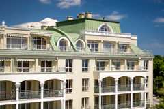 Classic building with arcs om balconies and green metal roof Royalty Free Stock Photo