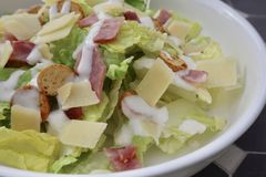 Classic Caesar Salad Bowl. Caesar salad with bacon, lettuce, croutons, cheese and dressing. Healthy and delicious. Fresh stock photo