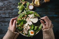 Classic Caesar salad. Female hands powring dressing to Classic Caesar salad with chicken breast in white ceramic plate. Served with ingredients above over old royalty free stock photography