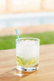 Classic caipirinha cocktail by a pool outdoors Royalty Free Stock Photos