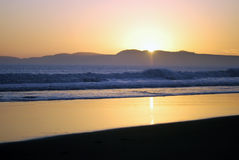 Classic California beach sunset. The sun sinks behind the mountains in a coastal bay stock images