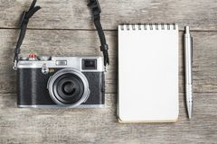 Classic camera with blank notepad page and gray pen on gray wooden, vintage desk. The concept of the list for the photographer in travels. Country style stock images