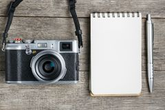 Classic camera with blank notepad page and gray pen on gray wooden, vintage desk. The concept of the list for the photographer in travels. Country style royalty free stock photos