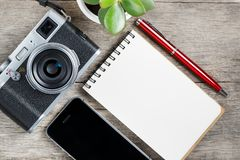 Classic camera with blank notepad page and red pen on gray wooden, vintage desk with telephone. Classic camera with blank notepad page and red pen on gray wooden royalty free stock photos