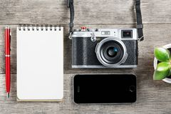 Classic camera with blank notepad page and red pen on gray wooden, vintage desk with telephone. Classic camera with blank notepad page and red pen on gray wooden royalty free stock image