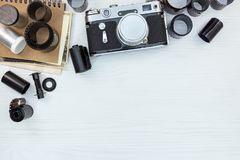 classic camera, negative films rolls and notebook on white wooden flat view Royalty Free Stock Photos